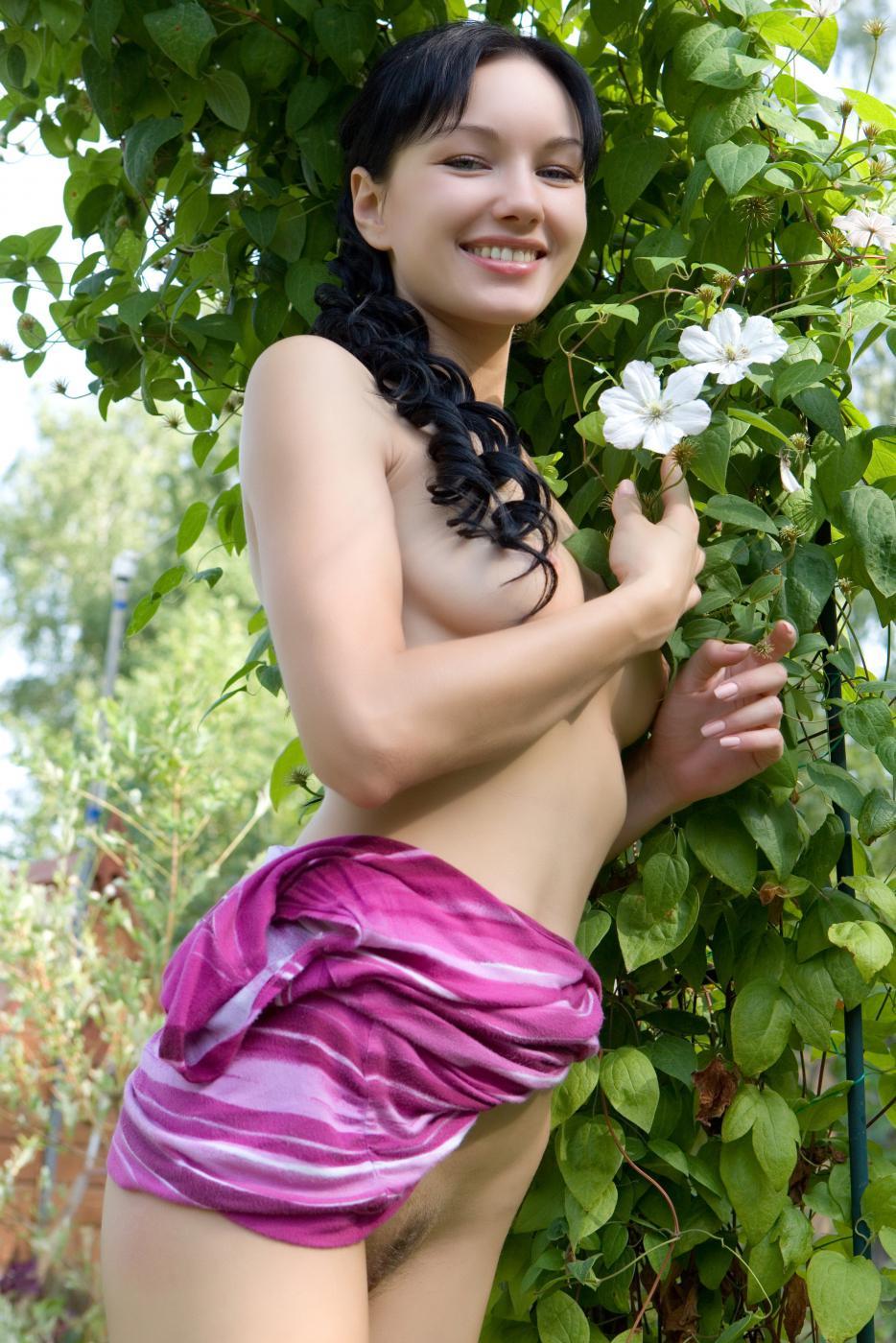 Роскошная модель с темными волосами Loreen A садится на траву и оголяет писю