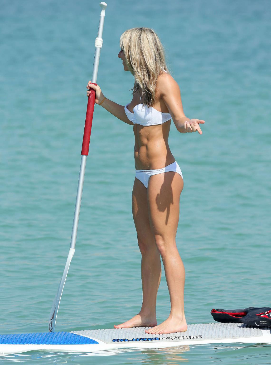 На пляже девка с маленькими формами снимается перед камерой папараци